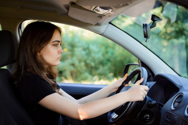 夏の日に車を運転する若い悲しい女の子。車内の機嫌が悪い女性ドライバー。