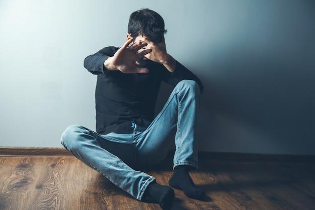 Молодой грустный человек рука знак остановки