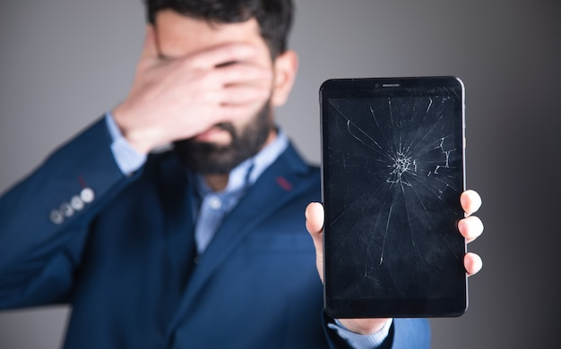 Young sad man holding broken screen tablet