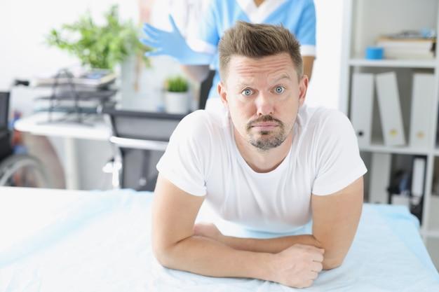 クリニックの肛門科医の前でソファに横たわっている若い悲しい男。がんと腸出血の概念を診断するための直腸指診