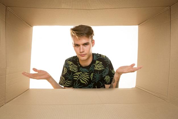 白で隔離された最大の郵便パッケージを開く若い悲しい男。中を見る段ボール箱の上に失望した男性モデル。
