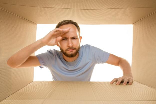 화이트 절연 가장 큰 우편 패키지를 여는 젊은 슬픈 남자. 골판지 상자 위에 실망한 남성 모델
