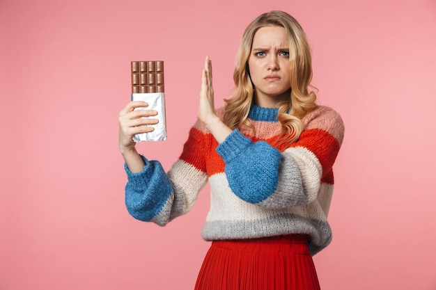 Young sad nervous pretty beautiful woman posing isolated over pink wall holding chocolate make stop gesture