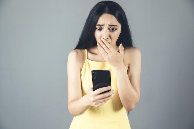 電話を持っている若い悲しいまたは驚いた女性