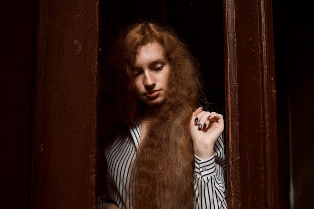 Young sad  red haired woman with long hair standing behind a closed glass door. raindrops on the glass