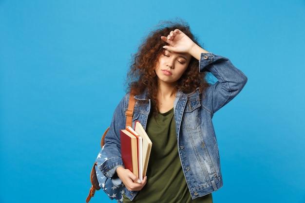 Il giovane studente triste in vestiti e zaino del denim tiene i libri isolati sulla parete blu