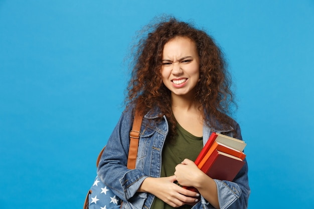 Young sad student in denim clothes and backpack holds books isolated on blue wall