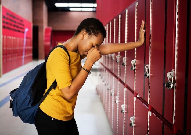 Young sad student on the hallway
