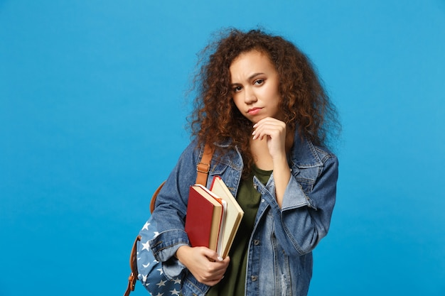Молодой грустный студент в джинсовой одежде и рюкзаке держит книги, изолированные на синей стене