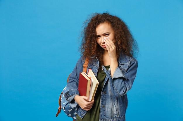 데님 옷과 배낭에 젊은 슬픈 학생은 파란색 벽에 고립 된 책을 보유