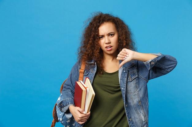 デニムの服とバックパックの若い悲しい学生は青い壁に隔離された本を保持します
