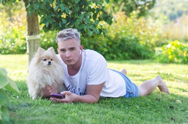 ドイツ語スピッツをなでる、ワイヤレスヘッドフォンで、スマートフォンで芝生の上の若い、悲しい、疲れた男。犬が飼い主を守ります。白いポメラニアンの男。
