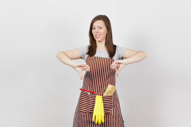 Молодая грустная расстроенная усталая плачущая домохозяйка в полосатом фартуке с тряпкой для чистки, скребком, изолированными желтыми перчатками