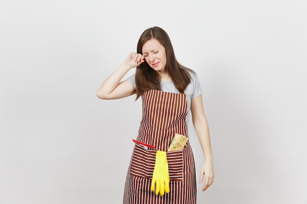 Young sad upset tired crying housewife in striped apron with cleaning rag, squeegee, yellow gloves isolated