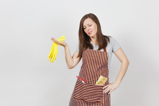 Молодая грустная расстроенная усталая потрясенная домохозяйка в полосатом фартуке с тряпкой для чистки в изолированном кармане. домработница держит запах желтых перчаток в раздвинутых руках