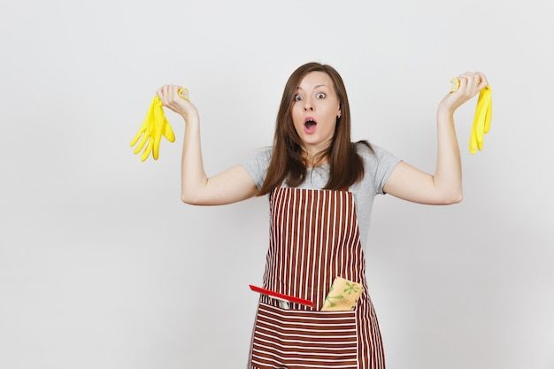 Young sad upset tired shocked housewife in striped apron with cleaning rag in pocket isolated. pretty housekeeper woman holding yellow gloves in spreading hands