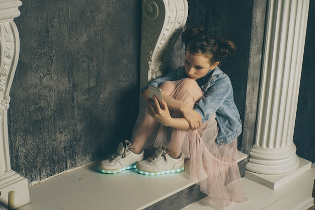 휴대 전화를 사용하는 젊은 슬픈 취약한 소녀는 십대 사이버 왕따 개념에서 스토킹되고 괴롭힘을당하는 온라인 학대 사이버 괴롭힘을 두려워하고 절망적으로 고통받습니다.
