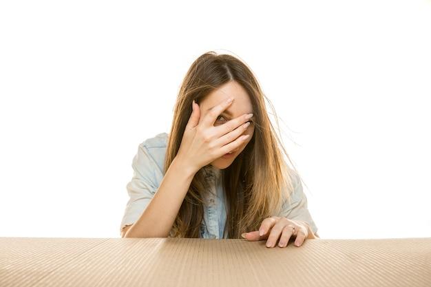 Giovane donna triste sul più grande pacchetto postale isolato su bianco. modello femminile sconvolto scioccato sopra la scatola di cartone che guarda dentro.