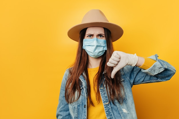 Young sad woman in hat looking disapprovingly at camera showing thumb down, wears medical face mask and denim jacket, isolated over yellow studio background.