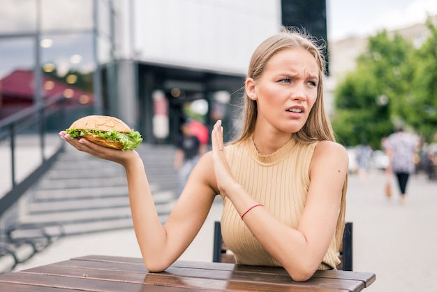 Young sad woman holding burger not satisfied while sitting in outdoors fast food