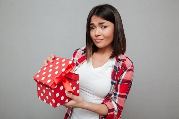 회색 벽 위에 선물을 들고 젊은 슬픈 여자.