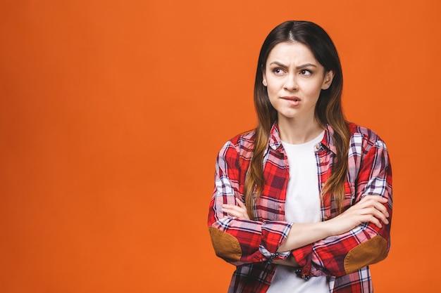 Молодая унылая женщина серьезная и обеспокоенная смотрящ взволнованное и заботливое выражение лица изолированная против оранжевой предпосылки в эмоции тоскливости и скорби.