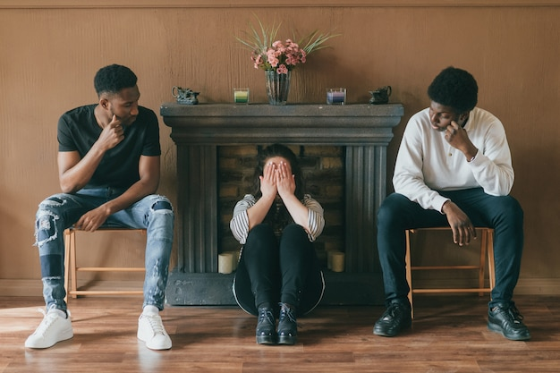 Young sad woman sitting on floor between two men and covering her crying face with hands