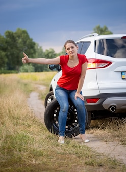 Young sad woman sitting on wheel at broken car in filed and hitchhiking