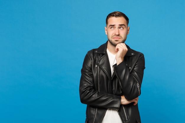 黒のジャケットの白いtシャツの若い悲しい心配無精ひげを生やした男は青い壁の背景スタジオの肖像画で隔離のあごに手の小道具を置きます。人々の誠実な感情のライフスタイルの概念。コピースペースをモックアップします。