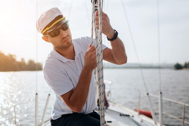 Молодой моряк в солнцезащитных очках и кепке держит и двигает веревки обеими руками. он спокоен и сосредоточен. молодой человек готовит яхту для плавания. на улице ясно.