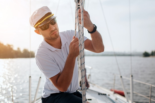 Young sailor in sunglasses and cap holds and moves ropes with both hands. he is calm and concentrated. young man is preparing yacht for sailing. it is sunny outside.