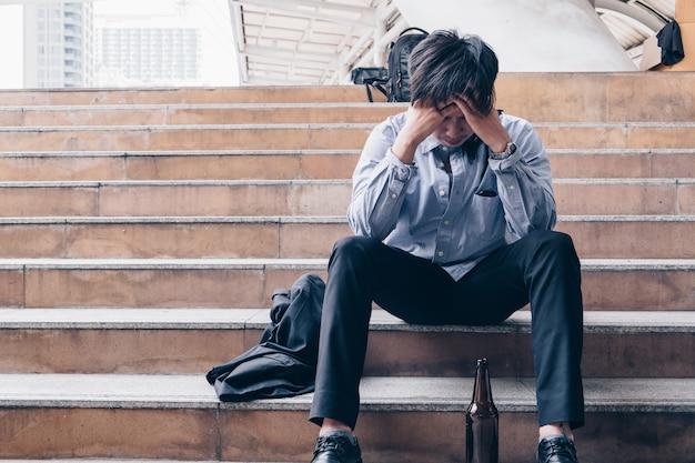 Молодой служащий сидит в стрессе и подавлен бутылочным алкоголем от безработицы