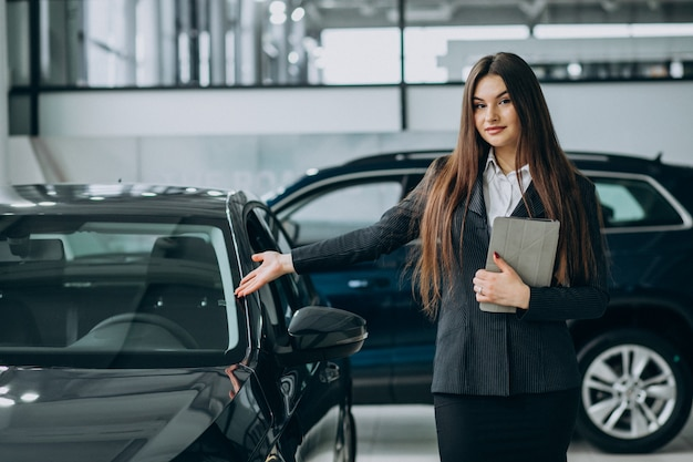 Young sales woman at carshowroom standing by the car