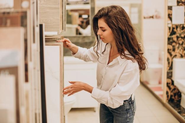 건물 시장에서 일하는 젊은 판매 여자