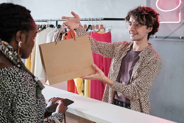 Young salesman giving the shopping bag with purchases to the customer in the clothes store