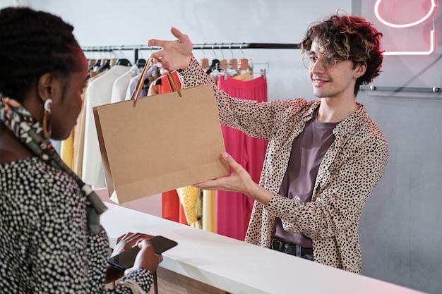 Молодой продавец дает сумку с покупками покупателю в магазине одежды