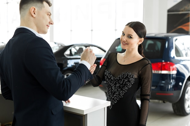 Young salesman receiving money and giving car's key to customer