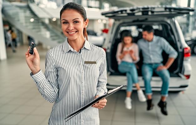 Молодая продавщица-консультант с ключом в автосалоне. на заднем плане пара сидит в открытом багажнике своей новой машины.