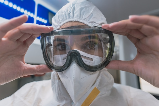 Young sanitary woman puts on a protective suit against viruses in an ambulance