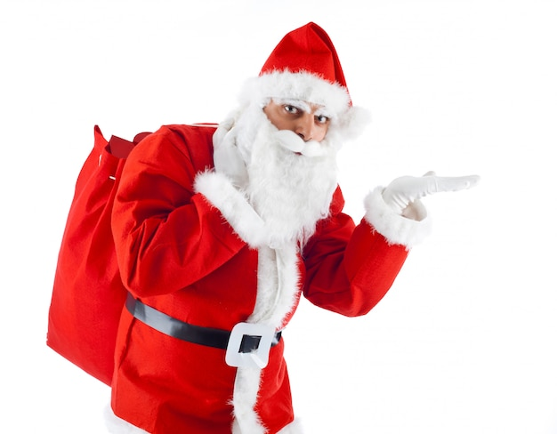 Young santa claus pointing on white background