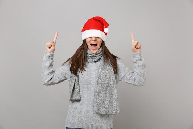 クリスマスの帽子で目を覆っているセーターの若いサンタの女の子は、灰色の背景で隔離された口を大きく開いたまま人差し指を指しています。明けましておめでとうございます2019お祝いホリデーパーティーのコンセプト。