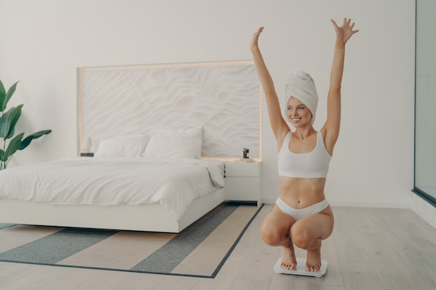 Young satisfied beautiful lady in perfect shape squatted on scales in white underwear and towel wrapped on head after morning shower in bedroom, throwing her hands up celebrating her weight loss