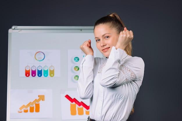 Молодая довольная деловая женщина после диаграмм конференции на сером изолированном фоне
