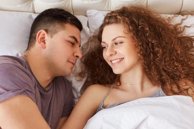 Молодые довольные пары лежат в удобной постели, смотрят друг на друга с любовью и о чем-то думают, приятно пообщаются