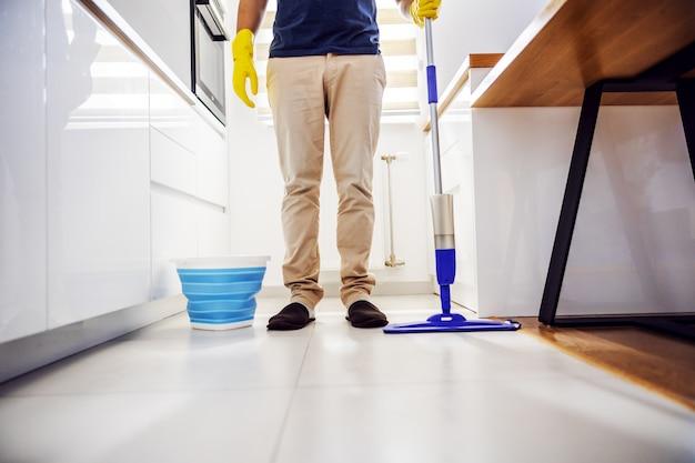 若い満足のモップを手にキッチンに立っています。キッチンの床はすべてきれいです。