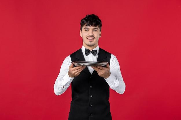 Giovane uomo soddisfatto cameriere in uniforme che lega farfalla sul collo tenendo il vassoio su sfondo rosso isolato