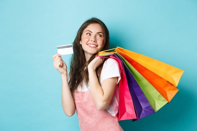Giovane donna soddisfatta che sorride, mostra la carta di credito in plastica e tiene in mano le borse della spesa, acquista con pagamento senza contatto, in piedi su sfondo blu.