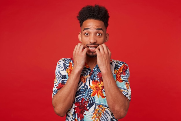 Young scared african american guy wears in hawaiian shirt, looking at the camera and bites nails, stands over red background.