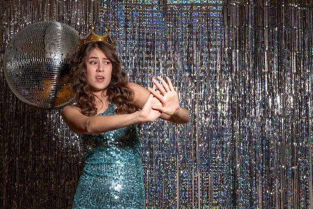 Молодая испуганная красивая дама в сине-зеленом блестящем платье с блестками с короной на вечеринке