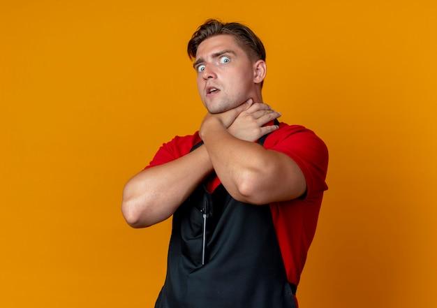 Il giovane barbiere maschio biondo spaventato in uniforme finge di soffocare se stesso con le mani isolate sullo spazio arancione con lo spazio della copia